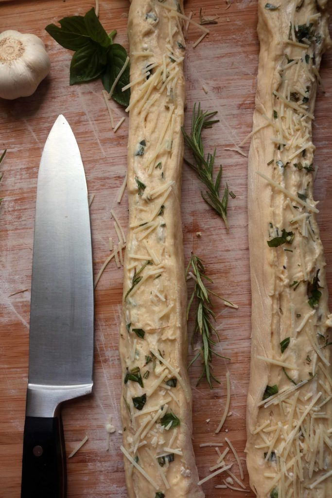 Slicing herb stuff cheese bread before braiding.