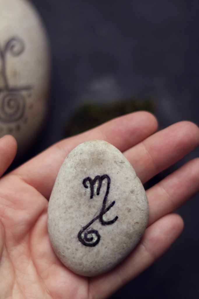 Sigil stone with astrological symbol for Scorpio and an inverted #9.